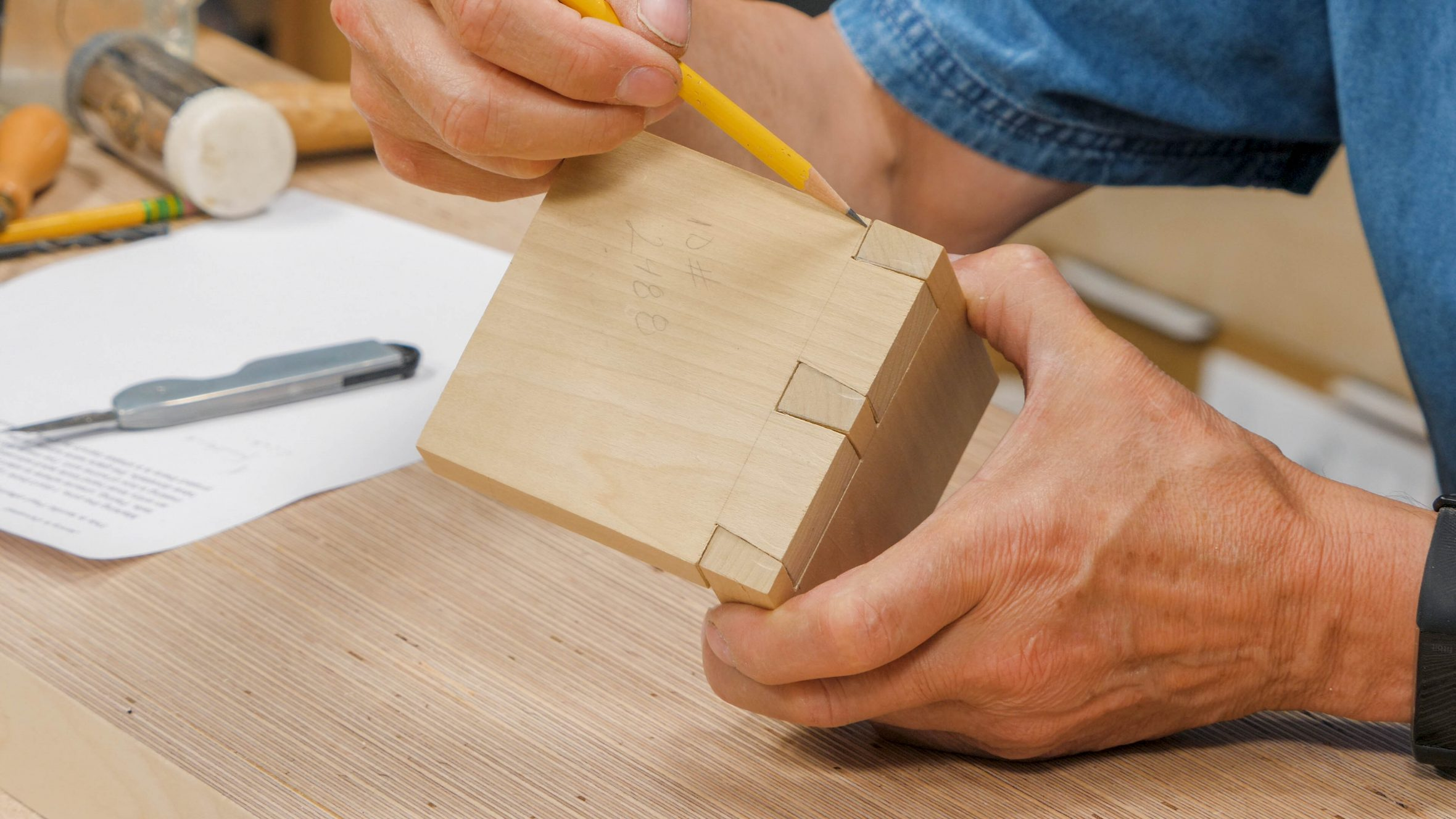 Pointing out the gaps in a dovetail joint using the point of a pencil.